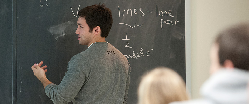 A student working a chemistry problem at the board.